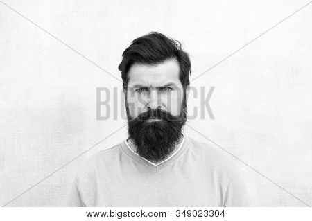 Strict face. Perceptions of male beauty around the world. Man bearded hipster stylish beard grey background. Stylish beard and mustache care. Hipster appearance. Beard fashion and barber concept. stock photo