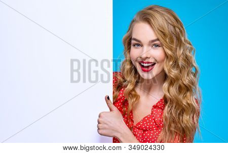 European  cheerful woman  shows big thumb  next to advertising banner. Young woman and large white banner. Smiling girl is standing next to a Billboard. Blonde girl and an empty ad sheet of paper. stock photo