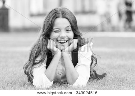 Winking to you. School break for rest. Adorable pupil. Girl kid laying lawn. Girl school uniform enjoy relax. Importance of relaxation. Little schoolgirl. Relax at school yard. Kid relaxing outdoors. stock photo