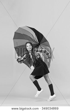 Towards knowledge. Schoolgirl with backpack. Schoolgirl daily life. Girl with umbrella. Rainy day. Happy childhood. Kid happy schoolgirl with umbrella. Fall weather forecast. Rainy september. stock photo