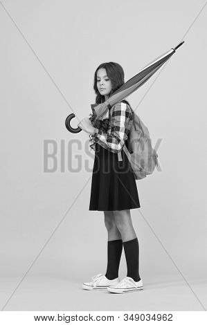 Schoolgirl daily life. Girl with umbrella. Happy childhood. Kid happy schoolgirl with umbrella. Fall weather forecast. Feeling carefree. Rainy september. Adorable small schoolgirl with backpack. stock photo
