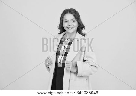 Yellow mood. Girl fashionable cute model wear yellow wool coat. Personal styling and bespoke tailoring. Feeling cozy and comfortable. Fancy child smiling face on yellow background. Yellow color. stock photo