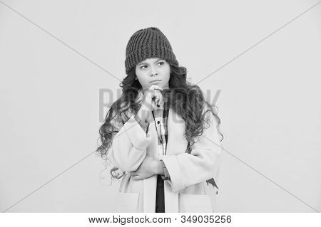 Decide. Adorable schoolgirl winter outfit. Schoolgirl daily outfit with backpack. Fashion accessory. Fancy schoolgirl. Girl little fashionable pupil wear knitted hat and jacket. Modern outfit. stock photo