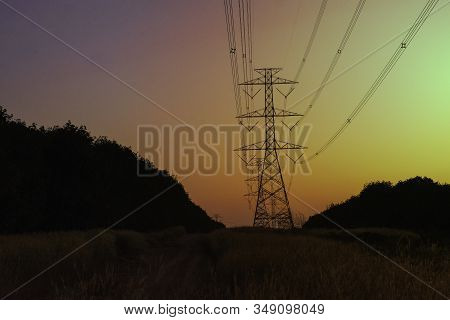 Electricity pole with silhouette sunset sky, Electricity pylon with shadow of tree in dawn time, Electricity power transmission line on sunset with copy space, Electricity pylon on orange sky stock photo