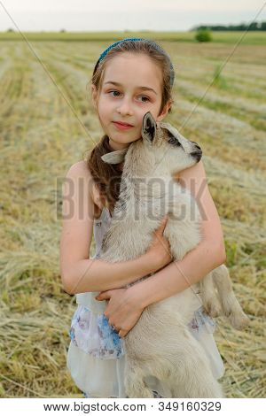 girl with baby goat on farm outdoors. Love and care. Village animals. happy child hugs goat, concept of unity of nature and man. Friendship of child and animals. Happy childhood. Girl and goat stock photo