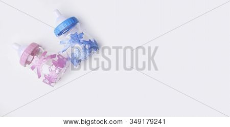 Is it a boy or a girl concept. Blue and pink toy bottles isolated on white. Twins baby shower. Baby announcement. Flat lay stock photo