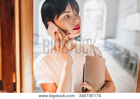 Close-up indoor portrait of busy young woman with red lips and trendy short hairstyle talking on phone. Amazing brunette girl in white shirt with laptop calling friend with serious face expression. stock photo