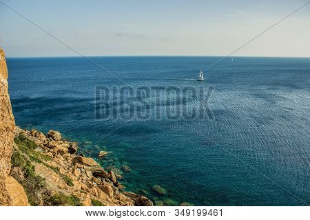 beautiful tropic panorama of small yacht on vivid blue water sea surface background near rocks shore line landscape view from above aerial shot, copy space for text stock photo