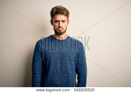 Young handsome man with beard wearing casual sweater standing over white background depressed and worry for distress, crying angry and afraid. Sad expression. stock photo