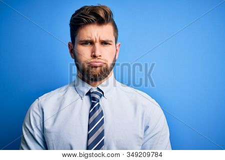 Young blond businessman with beard and blue eyes wearing elegant shirt and tie standing depressed and worry for distress, crying angry and afraid. Sad expression. stock photo