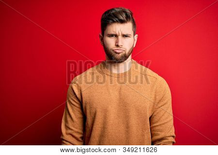Young blond man with beard and blue eyes wearing casual shirt over red background depressed and worry for distress, crying angry and afraid. Sad expression. stock photo