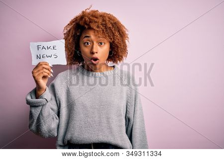 Young African American afro woman with curly hair holding paper with fake news message scared in shock with a surprise face, afraid and excited with fear expression stock photo