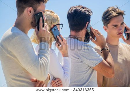 Mobile call. Conversation and discussion. Discussing project. Gadgets for communications. Mobile phone conversation. Friends chatting sky background. Mobile communication. People with smartphones stock photo