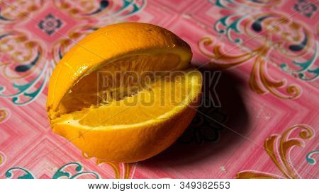 A fresh orange cut fruit on a pink background. It is the fruit of the citrus species Citrus in the family Rutaceae. stock photo
