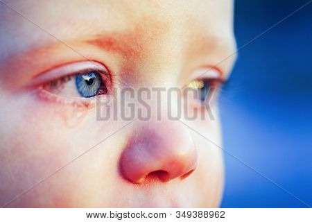 Cry baby with sky blue eyes. Little tender baby boy crying. Eye drop, tear drop of little sweetheart kid. Emotional baby miss his mom. Childhood concept stock photo