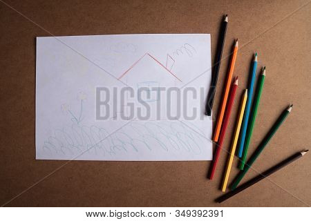 children's drawing and colored pencils lie on the table. children's creativity. children's problems. the child dreams of a cozy house. stock photo