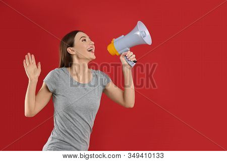 Young woman with megaphone on red background. Space for text stock photo