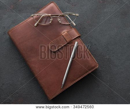 Brown leather notebook, pen and glasses on black background stock photo