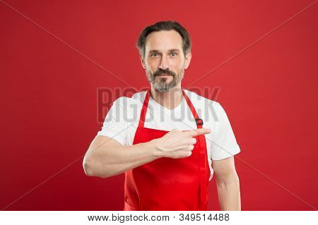 Giving instructions. Cook with beard and mustache wear apron red background. Man mature cook posing cooking apron. Fine recipe. Ideas and tips. Chief cook and professional culinary. Cook food at home. stock photo