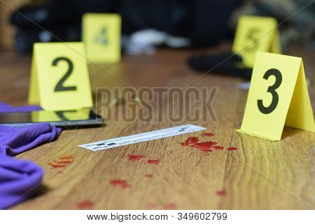 Id tents at crime scene after gunfight indoors. Blood and gun cartridges as evidence on crime scene investigation process stock photo