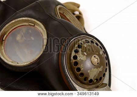 A closeup view of an antique Military grade gas mask over a white background with wear and tear distinguishing its age and vintage. stock photo