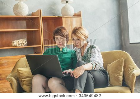Mature women with laptop indoors (lady 40s and 60s years old) stock photo