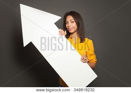 African American woman holding white empty arrow signboard on gray background stock photo