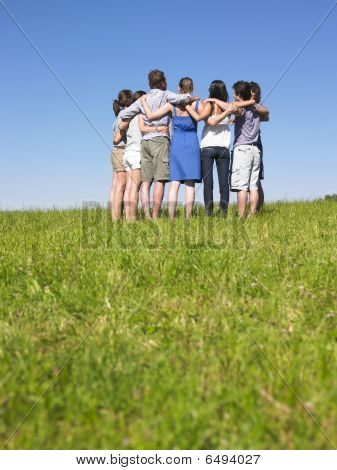 A group of people huddle in a field. Vertically framed shot. stock photo