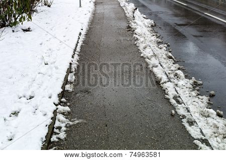 snow on sidewalk and street, symbol for accident risk and photo r���¤umpflicht stock photo