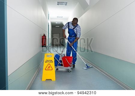 Portrait Of Young African Male Janitor Cleaning Floor In Corridor stock photo