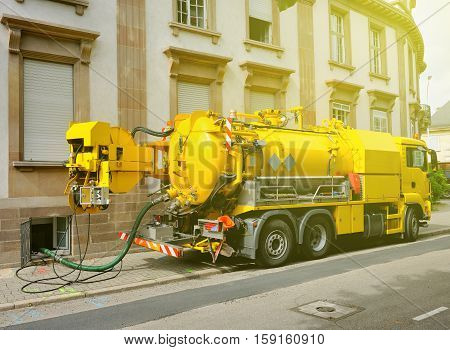 Working Sewage - sewerage - truck on city street in working process to clean up sewerage overflows cleaning pipelines and potential pollution issues from an modern building. This type of truck is used for residential septic systems or commercial sewage sy stock photo