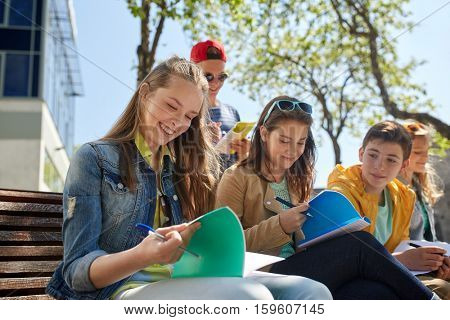 education, high school and people concept - group of happy teenage students with notebooks learning