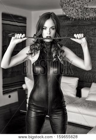 Sexy dominatrix in latex catsuit holding whip black and white stock photo
