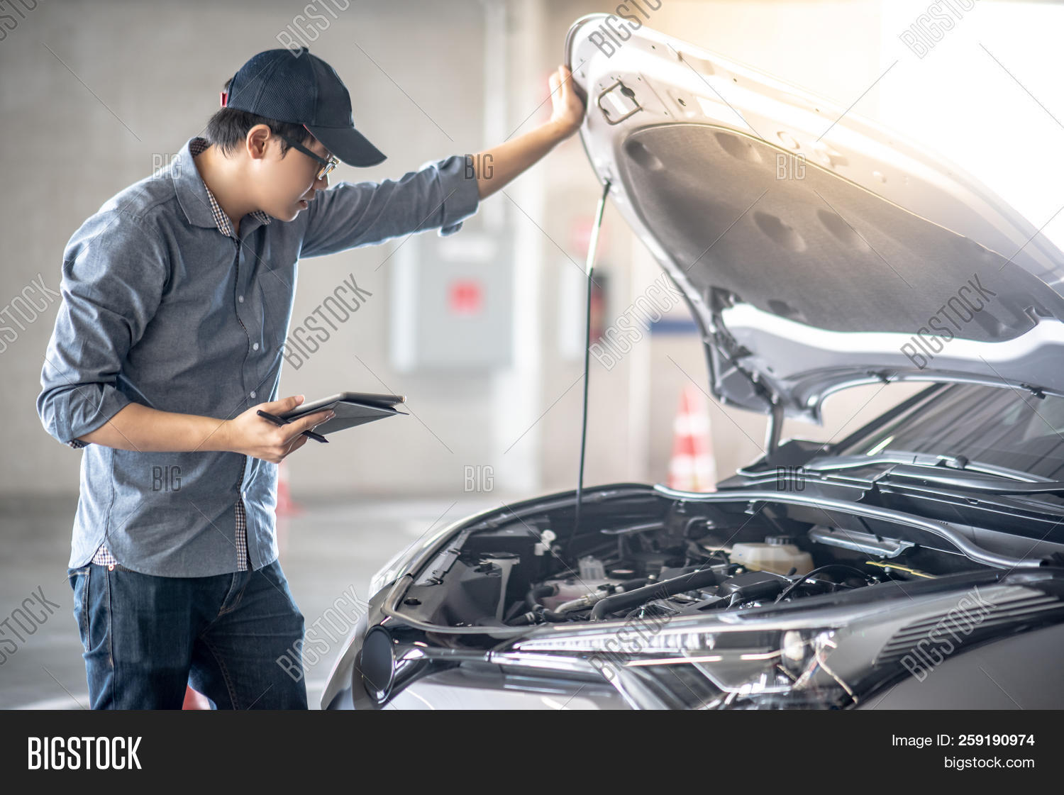 Asian Auto Mechanic Holding Digital Tablet Checking Car Engine Under The Hood In Auto Service Garage