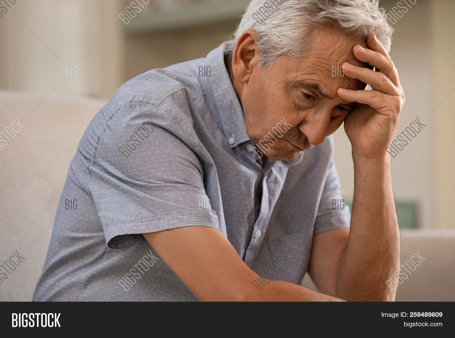 Thoughtful senior man sitting on couch. Depressed sad man sitting with hand on head thinking while l
