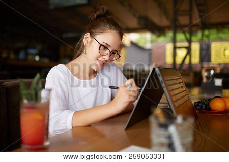 Digital artist drawing sketch with stylus on convertible 2 in 1 laptop display in tent mode. Mixed race multiethnic asian caucasian woman working on project design or writing notes on touchscreen. stock photo