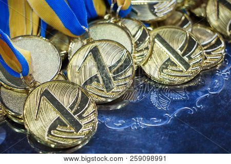 A lot of gold medals with blue yellow ribbons on a silver tray, awards of champions, sport achievements, first place, prize for the winner stock photo