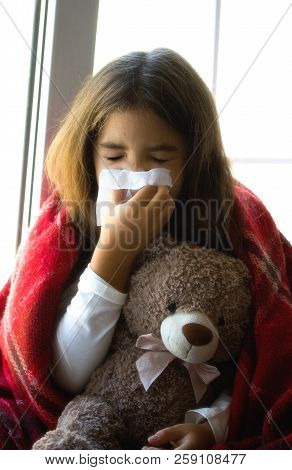 a sick little girl sits at the window wrapped in a blanket and blows her nose into a disposable napkin stock photo