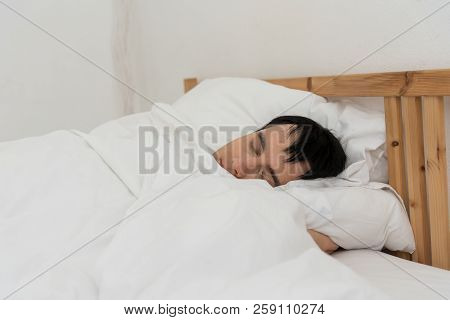 The young man was awakened by the morning alarm clock while on the bed.Shallow depth of field.unhappy from noisy sound of alarm clock and trying to turn it off. Hangover,lazy and sleepless concept. stock photo