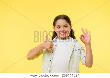 Excellent quality. Kid girl shows thumb up and ok gesture yellow background. Child highly recommend excellent quality. Girl happy smiling recommend high quality product. Sincere recommendation. stock photo