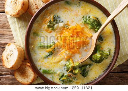 broccoli cheese soup served with toasted bread close-up in a bowl on the table. horizontal top view from above stock photo