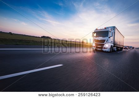 Loaded European truck on motorway in beautiful sunset light. On the road transportation and cargo. stock photo