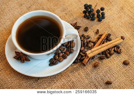 White porcelain cup of black flavoured coffee on burlap background with beans, cinnamon and stars of anise stock photo