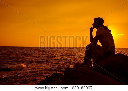 Silhouette women sitting alone on the rock. Mental health, PTSD and suicide prevention. stock photo