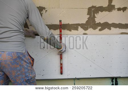 Man installing rigid styrofoam insulation board for energy saving on exterior wall of building. Rigid extruded polystyrene insulation for house improvement. stock photo