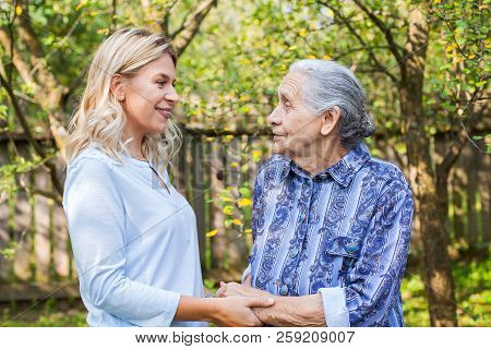 Friendly caregiver walking with old lady in the garden - Medical care stock photo