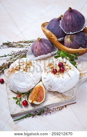 Mini pavlova cake with figs, cranberries and mint leaves stock photo