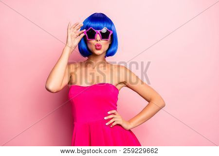 Careless, carefree woman with vivid modern hairdo hold hands on glasses, send kiss isolated on pastel pink background stock photo