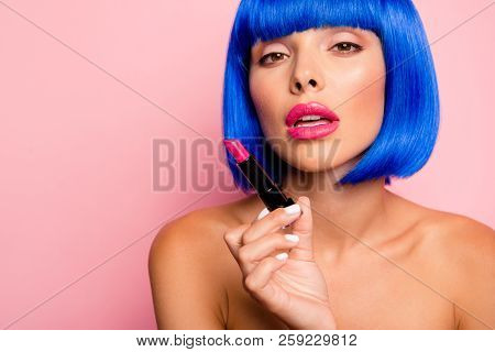 Cropped portrait of dreamy, alluring young person with modern bright hairdo, soft smooth perfect skin looking at camera and hold new lipstick isolated on pastel background with copy space for text stock photo