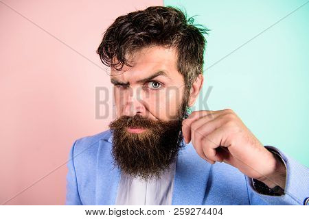 Ultimate moustache grooming guide. Barber tips growing moustache. Man bearded hipster twisting mustache pink blue background. Barber shop concept. Hipster handsome attractive guy with long beard stock photo